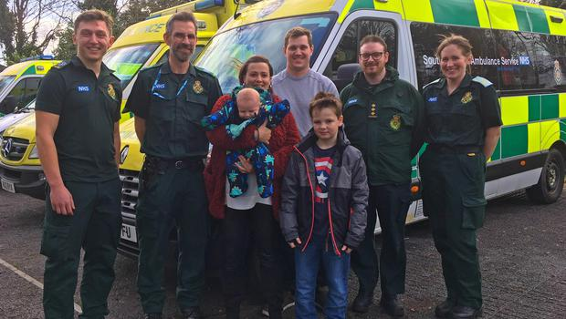 Jayne Rowland and Joshua Mogg with their newborn son Harry, and eight-year-old son Benjamin, alongside members of the ambulance service (South Western Ambulance Service/PA)