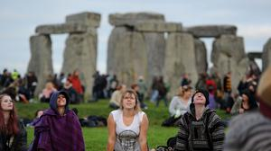 Members of the public take part in a yoga class as people gather at Stonehenge in Wiltshire to see in the new dawn