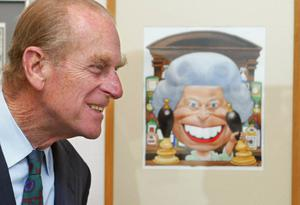 The Duke of Edinburgh next to a cartoon of the Queen standing behind the bar at the Old Vic pub from EastEnders at an exhibition (PA)