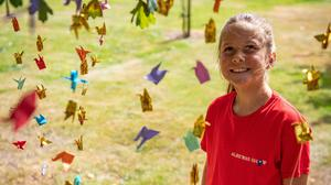 Emily Turner, nine, hangs origami peace cranes in the Anglo-Japanese Grove of Reconciliation at the National Memorial Arboretum in Alrewas, Staffordshire, to mark the 75th anniversary of the atomic bomb being dropped on Hiroshima (Jacob King/PA)