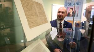 Ben Macpherson MSP, Minister for Europe, Migration and International Development, views two Robert Burns manuscripts which have gone on display in Glasgow (Andrew Milligan/PA)