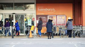 People observe social distancing while queuing outside a Sainsbury's supermarket (Danny Lawson/PA)