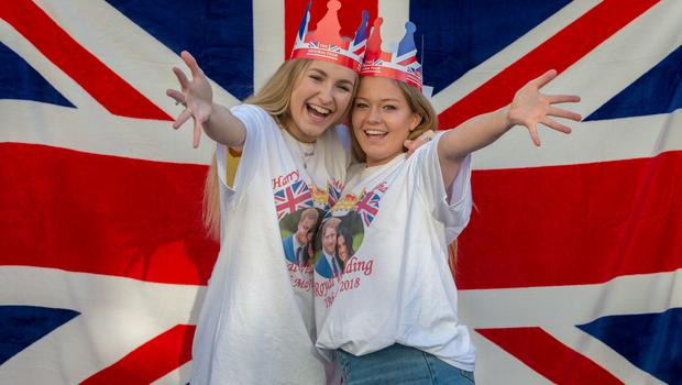 Reaching out: teenagers Kitty William and Annabelle West from Mayfair, London wait to cheer on the royal couple (James Hardisty/PA)