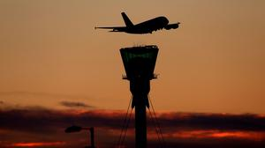 A plane leaves at sunset over Heathrow Airport (Steve Parsons/PA)