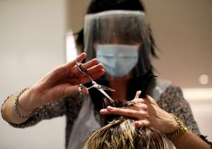 Stylist Tommy D'Amour cuts the hair of client Lea Jantz at Tusk Hair in Camden, North London. Hair salons are allowed to reopen but they cannot offer beauty treatments (Jonathan Brady/PA)