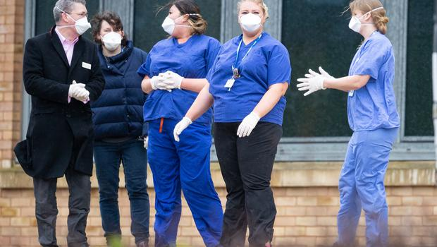 Members of staff wait as coaches carrying coronavirus evacuees arrive at Kents Hill Park Training and Conference Centre, in Milton Keynes (Aaron Chown/PA)