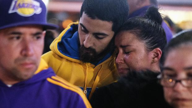 Fans pay their respects at a memorial outside the Staples Centre (Ringo H.W. Chiu/AP)