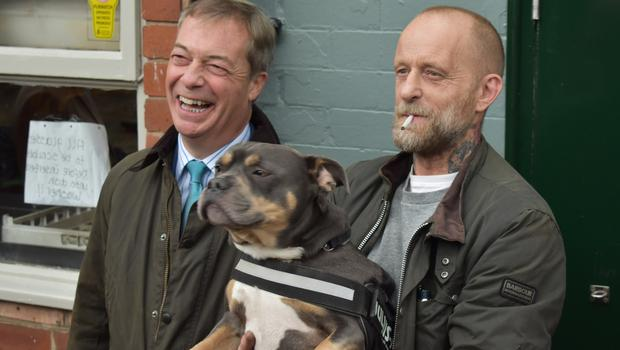 Brexit Party leader Nigel Farage poses for a photograph with party supporter Shaun Cottrell and his Staffordshire-French Bulldog cross Arthur outside the Wellington Inn in Nottinghamshire (Matthew Cooper/PA)