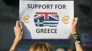 A demonstrator holds a sign during an earlier protest over Greece's debt repayments