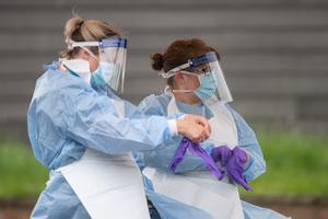 NHS staff put on personal protective equipment before carrying out Coronavirus tests at a testing facility in Bracebridge Heath, Lincoln (Joe Giddens/PA)