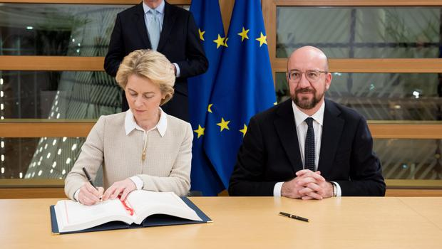 European Commission president Ursula von der Leyen and the president of the European Council, Charles Michel, sign the Brexit agreement (European Commission/PA)