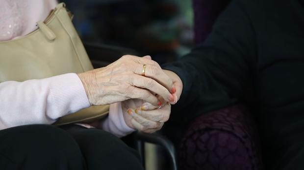 A care home resident holds hands with a family member (Aaron Chown/PA)
