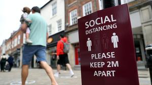 People walk past a social distancing sign on the high street in Winchester (Andrew Matthews/PA)