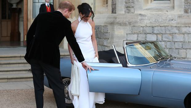 Harry helps Meghan into the car before driving to Frogmore House (Steve Parsons/PA)
