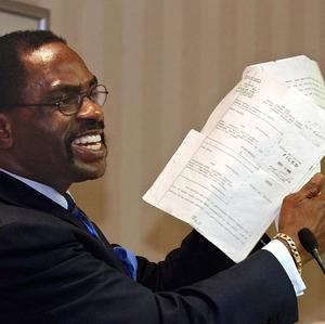 """Former boxer, Rubin """"Hurricane"""" Carter,  holds up the writ of habeas corpus that freed him from prison"""