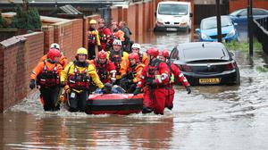 Fire and Rescue service members pull an inflatable boat that has been used to rescue residents trapped by floodwater in Doncaster (Danny Lawson/PA)