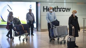 Passengers from the Holland America Line ship Zaandam walk through arrivals at Heathrow Airport after returning on a repatriation flight from Florida
