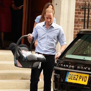 The Duke of Cambridge takes his new son to the car (PA)