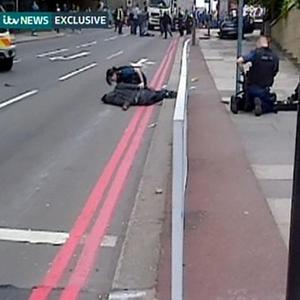 This video grab, from ITV News, shows two men being detained by police in John Wilson Street, Woolwich (ITV News/PA)