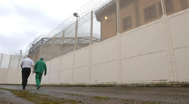 A prisoner and escort walk within the walls of Belmarsh maximum security jail in south east London