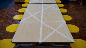 Tables are marked showing where children can sit during dinner time at a school (Jacob King/PA)