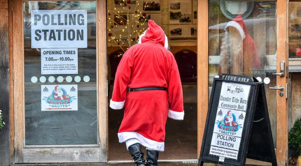 A man dressed as Father Christmas enters his grotto at the Dunster Tithe Barn near Minehead, Somerset, which is being used as a polling station (Ben Birchall/PA)