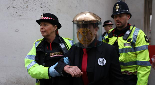 Police remove Extinction Rebellion protesters who glued themselves to the entrances of the London Stock Exchange (Isabel Infantes/PA)