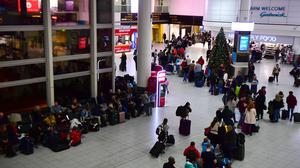 Stranded passengers queue for information (Victoria Jones/PA)