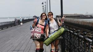 Festival goers walking along Ryde pier which is one of the main gateways to the Isle of Wight.