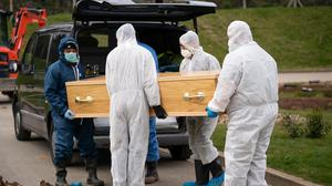 Undertakers wearing personal protective equipment carry a coffin (PA)