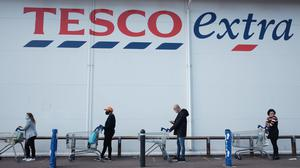 People practice social distancing outside a Tesco Extra store (Yui Mok/PA)