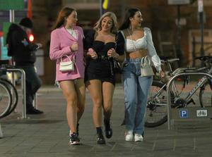 Three women in Liverpool, the night before new measures across the region are set to come into force (Peter Byrne/PA)