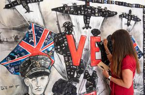 Sam Bailey painted a mural featuring Captain Tom Moore to mark the 75th anniversary of VE Day on Friday(Joe Giddens/PA)