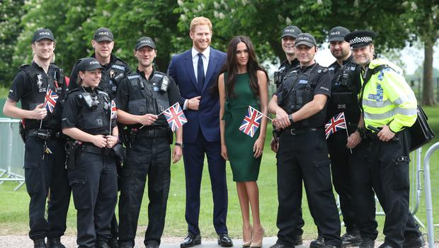 Police officers poses for photos with the Madame Tussauds' wax figures of Harry and Meghan (Jonathan Brady/PA)
