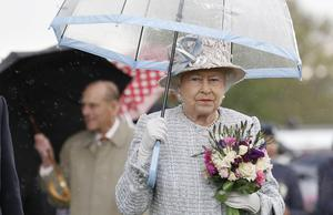 The Queen, under her umbrella, has two birthdays because of the British weather (Suzanne Plunkett/PA)