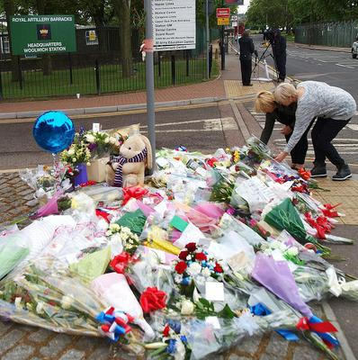 Two women lay flowers outside the Royal Artillery Barracks in Woolwich (PA)