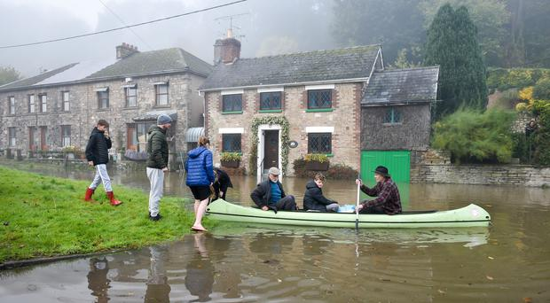 Paul Hayes ferries people to dry land after their family holiday accommodation in Lower Lydbrook was surrounded by floodwater (Ben Birchall/PA)