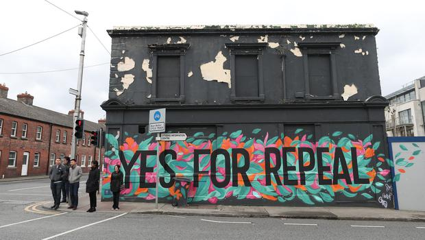 People walk past a mural in Dun Laoghaire (Niall Carson/PA)