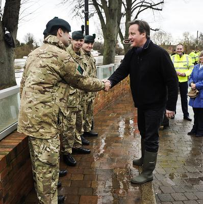 Prime Minister David Cameron chats with soldiers from the Royal Irish Regiment in flood-hit Upton-Upon-Severn