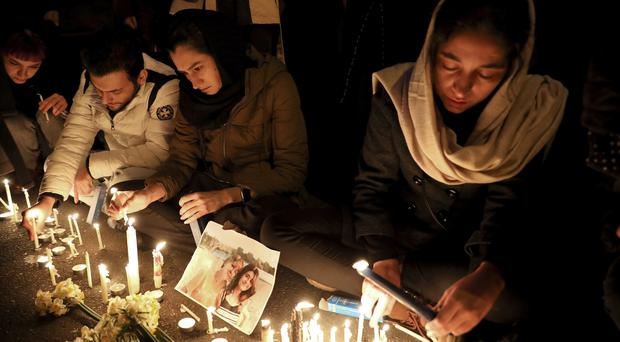 Iranians gather for a vigil for victims of the Ukrainian airliner crash at the gate of the Amri Kabir University in Tehran (Ebrahim Noroozi/AP)