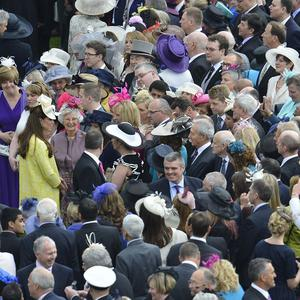 The Duchess of Cornwall, in yellow, is surrounded by well-wishers in the grounds of Buckingham Palace (PA)