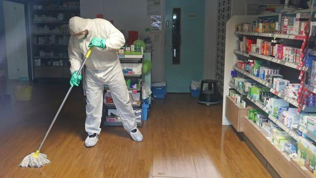 A man in protective clothing cleaning the County Oak Medical Centre GP practice in Brighton (Steve Parsons/PA)