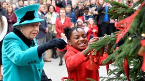 Queen Elizabeth II and Shylah Gordon, aged 8, attach a bauble to a Christmas tree during her visit to Coram, the UK's oldest children's charity, to open the Queen Elizabeth II Centre at its base in central London.