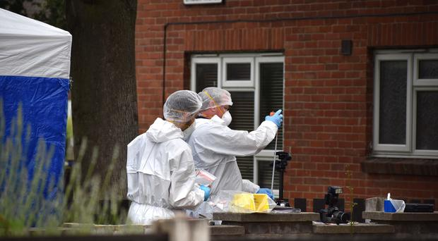 Forensic officers near the entrance to a flat in Long Eaton, Derbyshire, following the death of a man in a fire (Matthew Cooper/PA)