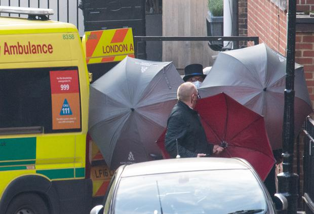 Staff shield the exit with umbrellas alongside an ambulance outside the rear of the King Edward VII Hospital (Dominic Lipinski/PA)