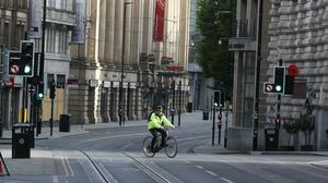 A cyclist on the way to work in Manchester as the UK continues in lockdown (PA)