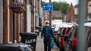 A man wearing PPE walks down a street in the North Evington area of Leicester (Jacob King/PA)