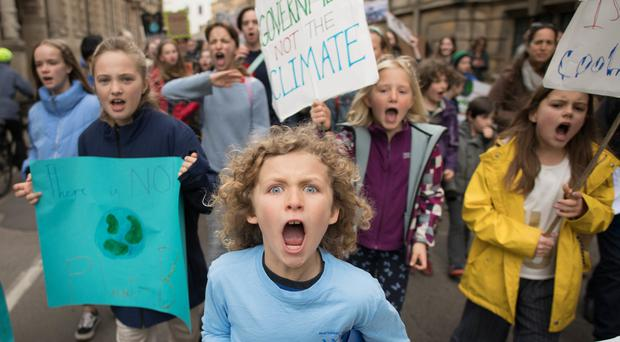 Schoolchildren marching through Cambridge city centre to take part in a 'die-in' climate change protest (Stefan Rousseau/PA)