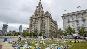 Workmen clear up rubbish left outside the Liver building in Liverpool after fans celebrated in the city last night following Liverpool FC winning the Premier League on Thursday night (Peter Byrne/PA)