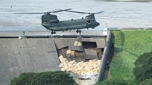 An RAF Chinook helicopter flies in sandbags to help repair the dam at Toddbrook reservoir near the village of Whaley Bridge in Derbyshire after it was damaged by heavy rainfall (PA)